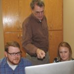 Hughes teaching two students in front of a computer
