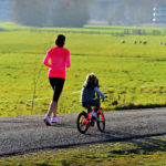 Picture of a woman running next to a child biking