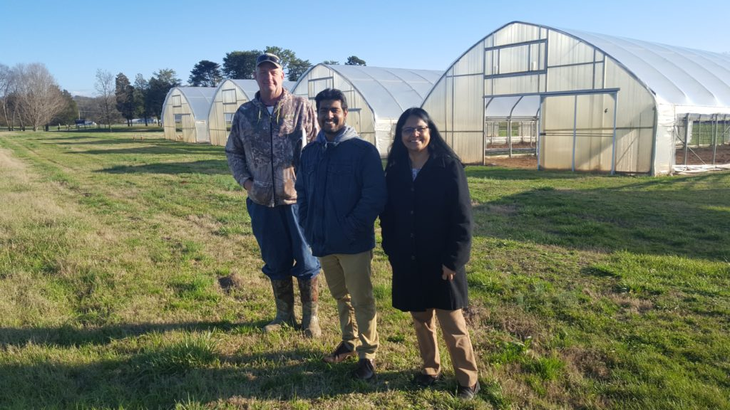 Picture of three people standing in front of greenhouses.