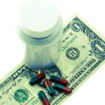 Picture of pills on top of a dollar bill