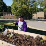 A Tennessee School for the Deaf student waters plants in a raised bed