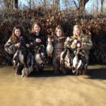 Four female hunters stand in a pond with their harvested ducks.