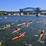 A large group of student kayak on the Tennessee River while a spanning bridge sets the background