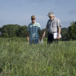 Johnny Richwine and Pat Keyser inspect a field of native grasses.