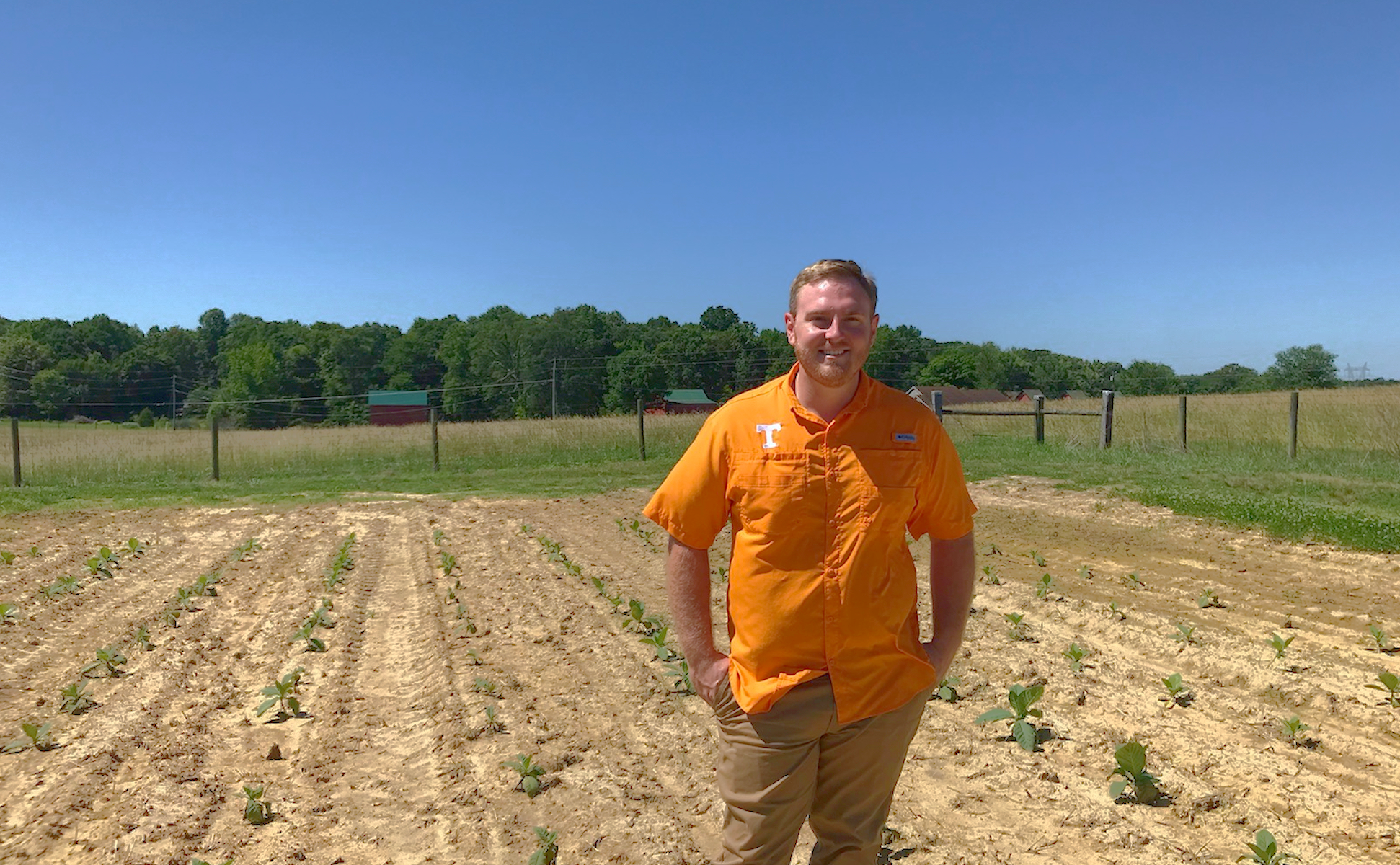 Associate professor Mitchell Richmond stands in front of a field at the Northeast Research and Education Center